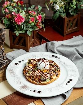 ワッフルフルーツバナナキウイフルーツバニラアイスクリームとチョコレートソース
