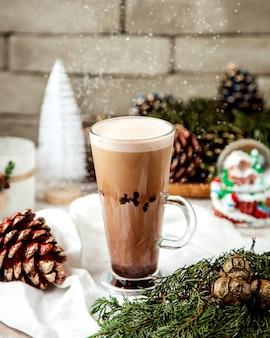 クリスマスの飾りの横にあるラテのカップ