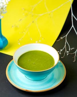 Тарелка зеленого овощного супа в бирюзовой керамической миске