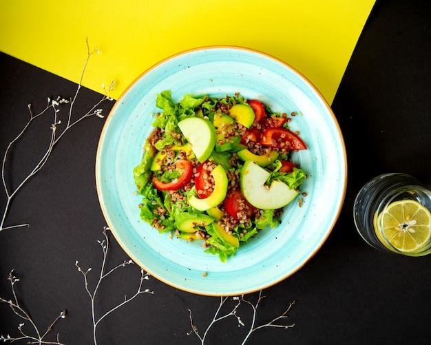Вид сверху полезного салата с авокадо, зеленым яблоком, томатным салатом и гречкой