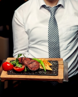 グリルソーセージケバブとトマトとコショウのグリルパンの大皿を保持ウェイター