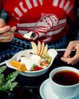 Женщина ест шоколадный вулкан и мороженое с кусочками фруктов и орехами