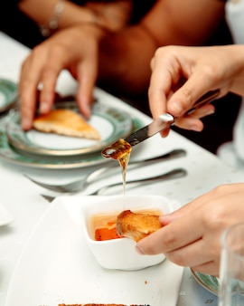 朝食に蜂蜜とトーストを食べる女性