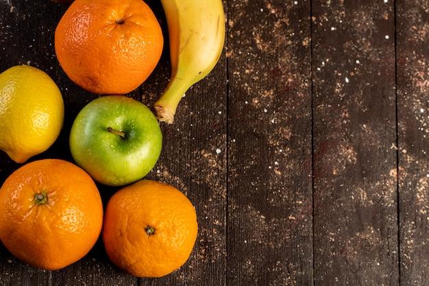 Банан, лимон, яблоко и мандарин на деревянном столе