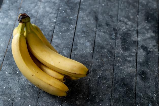 木製のテーブルに新鮮なバナナ