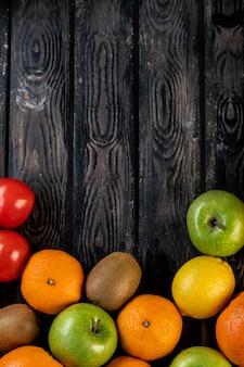 Лимоны, яблоки, киви и мандарины на деревянном столе
