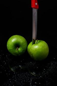 Две зеленые яблоки с ножом на черном