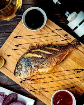 テーブルの上の木の板に魚のフライ