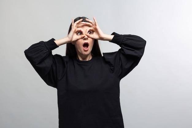 Женщина в черном свитере демонстрирует очки