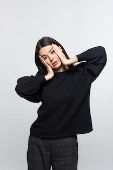 Женщина в черном свитере демонстрирует головную боль