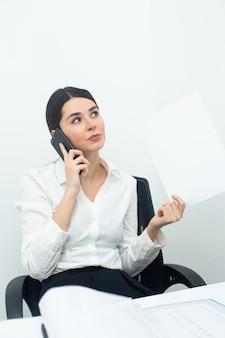 Женщина думает во время разговора по телефону