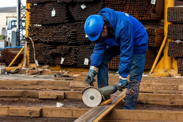 Рабочий режет железо инструментом