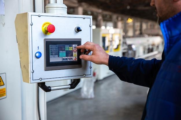 Работник использует панель управления на заводе