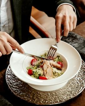 Салат цезарь с курицей, листьями салата, помидорами и тертым сыром