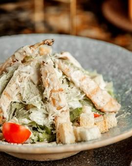 Салат цезарь с курицей, листьями салата, помидорами, крекерами и тертым сыром