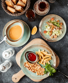 Куриный стейк с картофелем фри и кетчупом, подается с супом и салатом цезарь