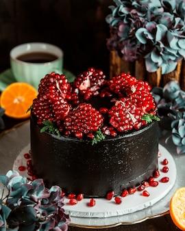 皮をむいたザクロで飾られたチョコレートケーキ