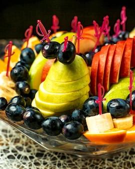 Фруктовый салат с яблоками, апельсинами, бананами, виноградом и грушами