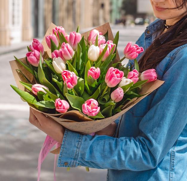 女の子の手でピンクのチューリップの花束