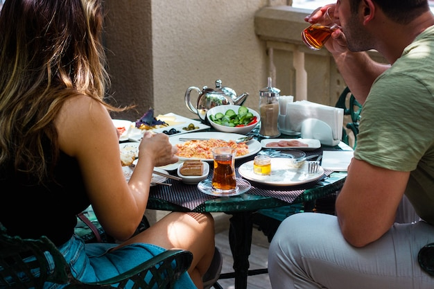 Пара завтракает на веранде кафе
