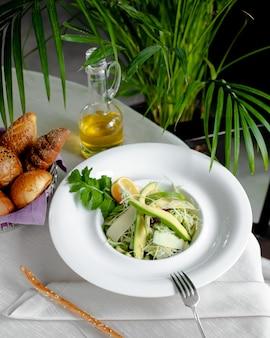 Салат из авокадо с тертым сыром и лимоном, подается с хлебом