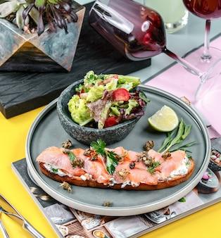 Бутерброд с лососем с овощами в тарелке