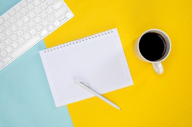 Чашка кофе, беспроводная клавиатура и блокнот