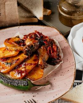 Жареная курица с картофелем в тарелке