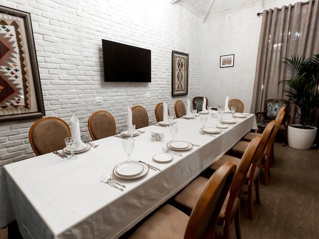 白い石の壁と茶色の椅子のあるレストランの個室