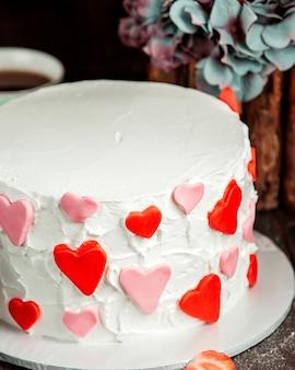 Белый кремовый торт украшен розовыми и красными сердечками