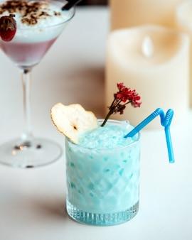 Хрустальное стекло синего коктейля, украшенное ломтиком сушеной груши