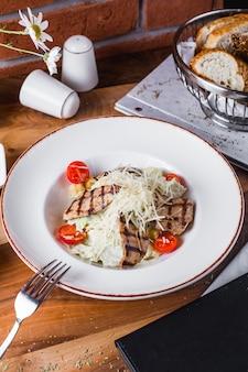 Мясной салат с листьями салата, помидорами и тертым сыром
