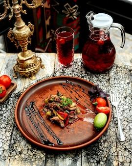 Тарелка жареных ломтиков баранины с желтым красным и зеленым перцем и зеленью