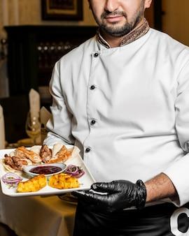 Шеф-повар держит блюдо из куриного ягненка и шашлыка с кислым соусом и лепешкой
