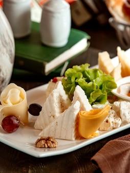 チェダーホワイトチーズヤギチーズブドウとナッツのチーズプレートのクローズアップ
