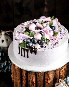 ライラックピンクの装飾とブドウで飾られたライラックのクリーミーなケーキのクローズアップ