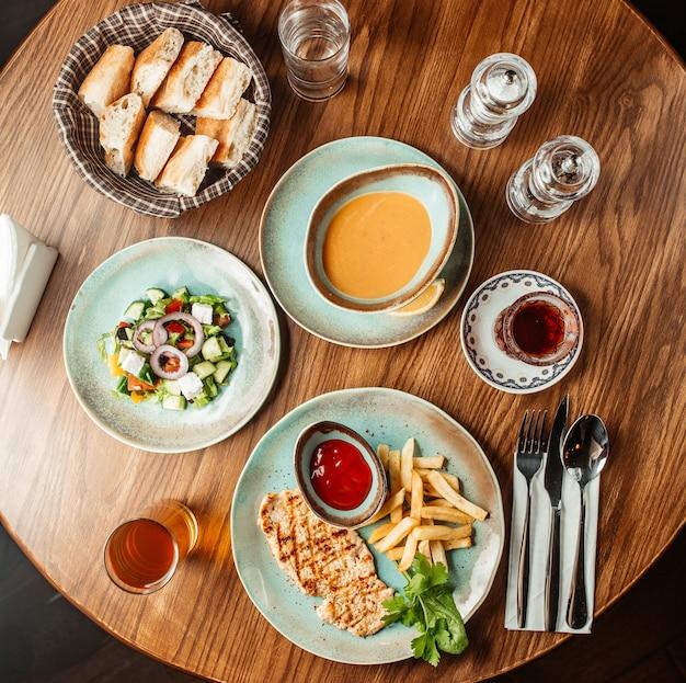 Вид сверху на обед с курицей-гриль, чечевичным супом, хлебом и греческим салатом