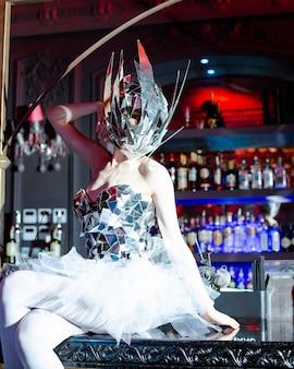Женщина с зеркальной маской и зеркальным корсетом сидит на барной стойке