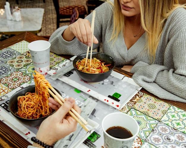Пара ест томатные спагетти с палочками