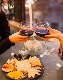 カップルはチーズプレートを添えてワインを飲む
