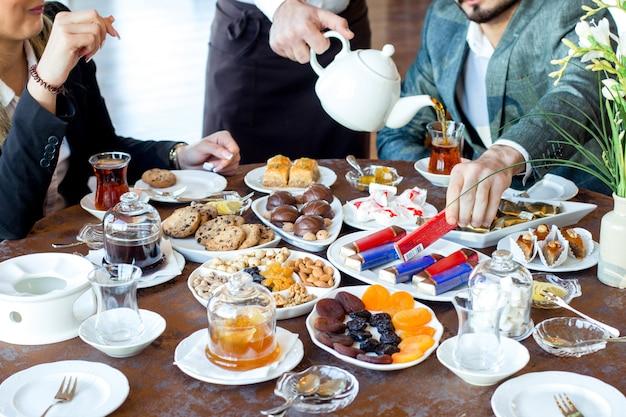 Пара пьет чай с печеньем, сладостями, сухофруктами и орехами и пахлавой