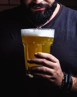 男はビールのグラスを握る