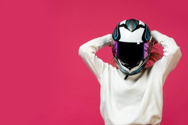 Женщина в белом пуловере с мотоциклетным шлемом