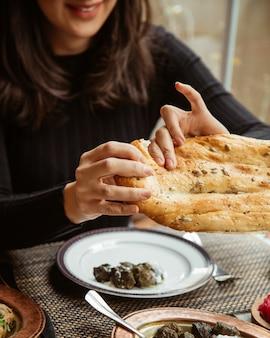少女はヨーグルトとドルマを食べ、パンを引き裂きます