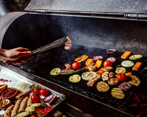 Мужчина жарит овощи на гриле с колбасками