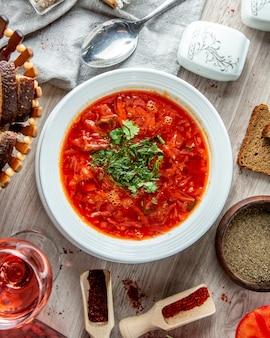 茶色のパンとソフトドリンクのスライスと伝統的なウクライナのボルシチ