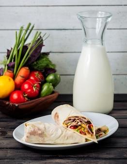 テーブルの上の牛乳と肉のブリトー