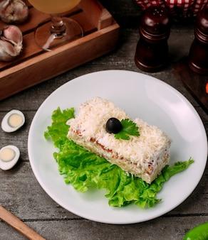 テーブルの上の白いボウルにオリーブのミモザサラダ