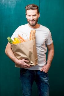 食べ物がいっぱい入ったバッグを持つ男