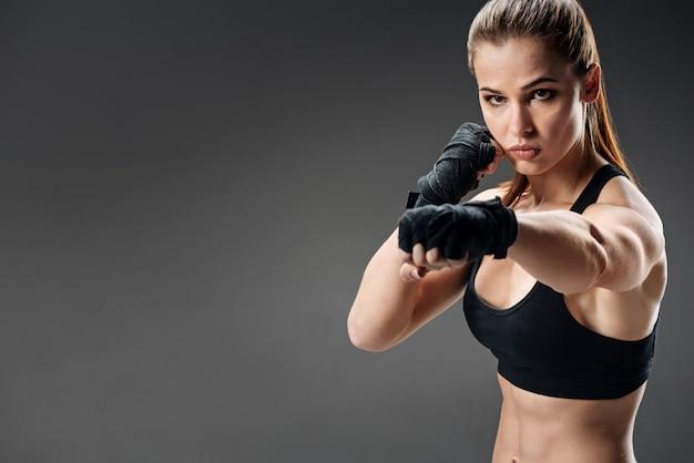 灰色のボクシングのスリムな女性